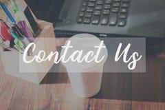 Contattici messaggio sugli impianti del dispositivo il concetto del servizio clienti della corrispondenza del fondo della tavola Immagine Stock