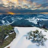 Conte d'hiver avec le coucher du soleil de montagne Images stock