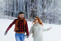 Conte de fées de Noël Le couple heureux tient des mains et fonctionne gaiement le long de la forêt neigeuse Photo libre de droits