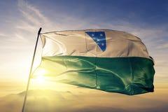 Contea di Valga del tessuto del panno del tessuto della bandiera dell'Estonia che ondeggia sulla nebbia superiore della foschia d immagine stock