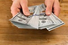 Conteggio dell'uomo i nuovi dollari americani sulla tavola di legno fotografia stock