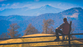 Contemplate the valley. Instagram stylisation. Man sitting on a wooden fence and contemplates the carpathian mountain valley. Instagram stylisation Stock Photo