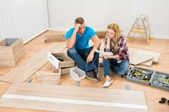 Contemplated couple with disassembled furniture. Portrait Of Contemplated Couple With Disassembled Furniture Parts In New Home Stock Images