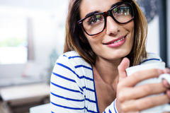 Contemplated young woman smiling while holding coffee Stock Photos