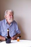 Contemplatieve Hogere Mens met Fles en Glas Stock Fotografie