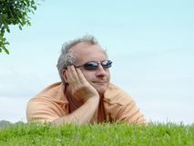 Contemplating. A man on the grass stock photos
