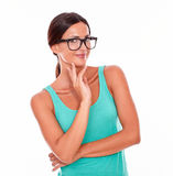 Contemplating brunette woman with green tank top. Contemplating brunette woman in green tank top looking at the camera with a reflective gesture of a hand on her Stock Photography