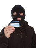 Contemplating Burglar Holding Credit Card. Burglar Wearing Mask Holding Credit Card Over White Background stock photo