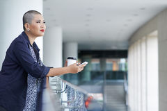 Contemplating business woman. Beautiful bald woman drinking coffee and contemplating at the business center Stock Images