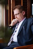 Contemplating businessman. Portrait of contemplating mature businessman in glasses Royalty Free Stock Images