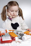 Contemplating child. Contemplating little girl behind pile of medications Stock Image
