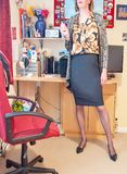 Contemplating the day ahead!. A smart and casually dressed Woman wearing a black pencil skirt and print blouse and cardigan stood in an office contemplating the royalty free stock image