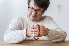 Contemplating elderly woman with rosary Stock Photos