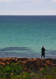 Contemplating Life. A man in a straw hat contemplating life across a tranquil ocean Royalty Free Stock Photo
