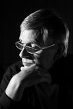 Contemplating man. Senior man with glasses contemplating royalty free stock photo