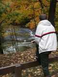 Contemplating nature. Man with apple looking at rushing stream and fall colors Stock Photos