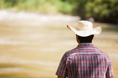 Contemplating Nature. A man with a hat contemplating a beautiful landscape by a riverside Royalty Free Stock Image