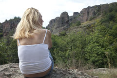 Contemplating Nature. Woman sitting on a rock Stock Photo