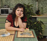 Contemplating over cake. Beautiful buxom lady contemplating over cake Royalty Free Stock Image