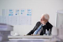 Contemplating senior entrepreneur. Portrait of contemplating senior entrepreneur sitting at is workplace and looking at the window Royalty Free Stock Photos
