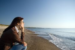 Contemplating the sun. A woman sitting at a beach at the sea, in a contemplating and thinking pose, facing the sun Stock Photo