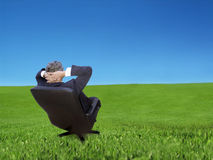 Contemplation. Businessman relaxing on a office chair enjoying the view Royalty Free Stock Image