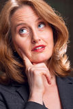 Contemplation. Businesswoman resting hand on chin with expression of contemplation royalty free stock photography