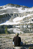 Contemplation. A hiker sits in silence amidst the mountains Stock Photography