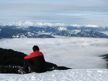 Contemplation. A skier takes a break to contemplate the view from the top of a mountain stock photography