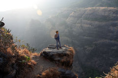 Contemplation. A young Indian guy contemplating on a rock near a valley Royalty Free Stock Photography