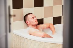 Contemplation in the bathroom. Young man relaxing in the bathtub full of foam stock photo