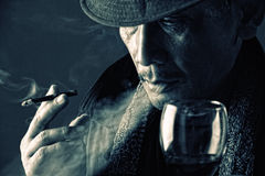 Contemplation of a crime lord. Close up face of tired old crime lord smoking a cigarette and drinking a glass of wine in the dark royalty free stock image
