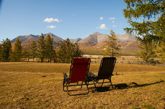 Contemplation. Deckchairs in the valley with views of the mountains are not stock photo