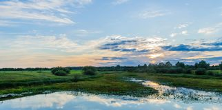 Contemplation of a magical sunset with reflections of the sky in the river on the natural horizon. Panorama of the glow of yellow and red lights of the sky royalty free stock photography