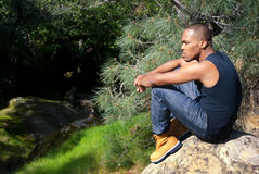 Contemplation in Nature. Young African American man sitting alone in contemplation in a forest stock photos