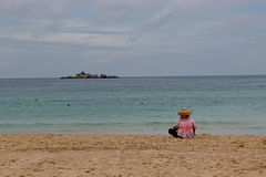 Contemplation at the sea shore. Chinese woman sitting on the beach and looking at the sea Royalty Free Stock Photography