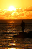 Contemplative 2. Man standing on the rocks at sunset royalty free stock photo