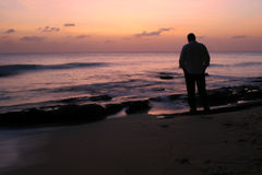 Contemplative. Man standing on the beach at sunset royalty free stock image