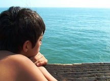 Contemplative Boy. Boy looking out over the ocean royalty free stock images