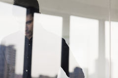Contemplative businessman looking down on the other side of a glass wall Royalty Free Stock Photos