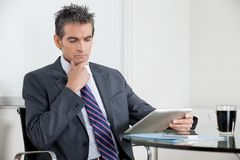 Contemplative Businessman Using Digital Tablet In Royalty Free Stock Photo