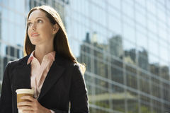 Contemplative Businesswoman With Drink Outside Building Stock Photo