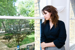 Contemplative businesswoman looking out the window Stock Photos