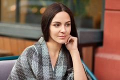 Contemplative dark haired beautiful young woman deep in thoughts, keeps hand near face, wrapped in plaid, enjoys calm atmosphere, royalty free stock image