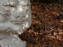 Contemplative garden gargoyle with brown fall leaves. stock image