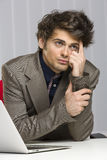 Thinking business guy. Portrait of thinking handsome young business guy sitting at desk in his office Stock Image
