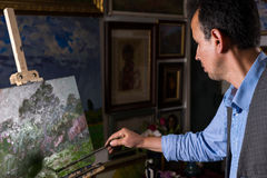 Contemplative male painter ending his masterpiece Royalty Free Stock Image