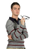 A Contemplative Man Holds His Glasses. A man contemplates a serious issue royalty free stock photo