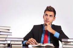Contemplative man reads at desk Royalty Free Stock Photography