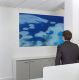 Contemplative mid-adult businessman looking at painting on wall in office Stock Image